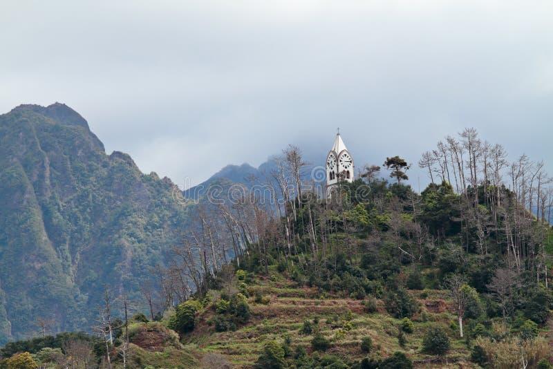 Montagna nebbiosa con la torre di chiesa bianca fotografia stock