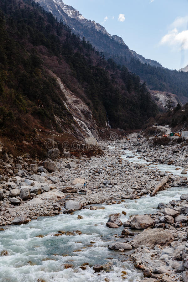 Montagna nera con neve sulla cima Sulla terra è il fiume congelato con la pietra ed il ghiaccio bianchi alla valle di Chopta e di fotografie stock