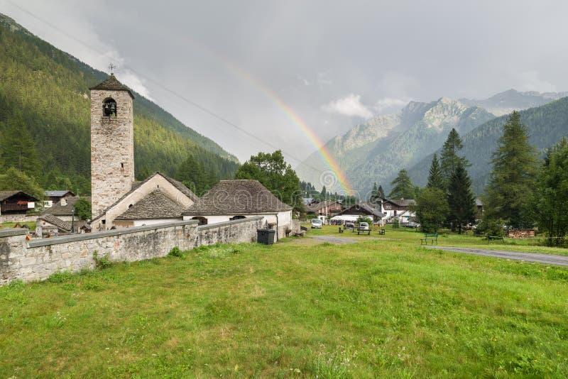 Montagne avec l'arc-en-ciel et l'église en pierre caractéristique Village alpin traditionnel, Macugnaga, Piémont, Italie photos stock