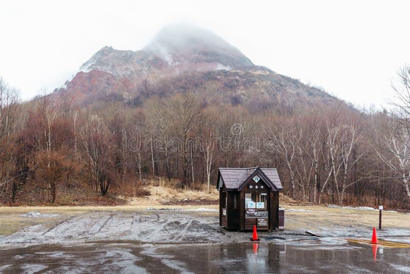 Montagne avec la neige et le brouillard sur le dessus, arbres et maison de garde ci-dessous au carpark du parc d'ours de Noboribe photos libres de droits