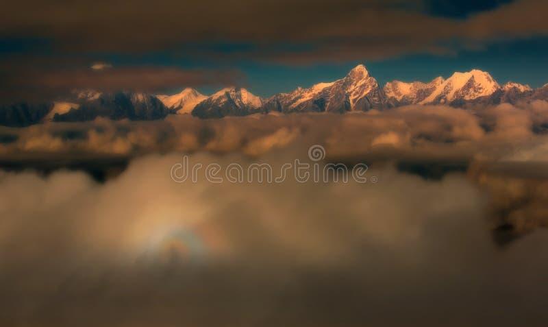 Montagne brillanti dietro le nuvole fotografia stock libera da diritti