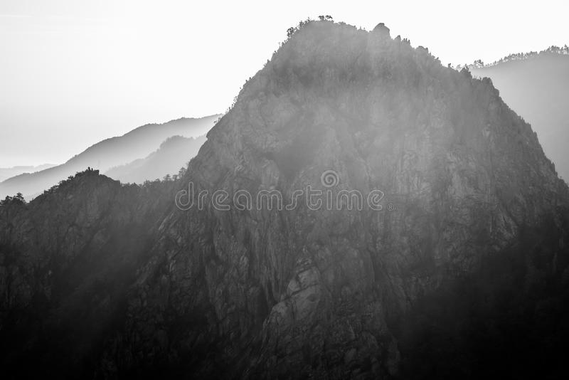 Montagne contrastée avec le tranchant, noir et blanc avec le fond de smokey photos stock