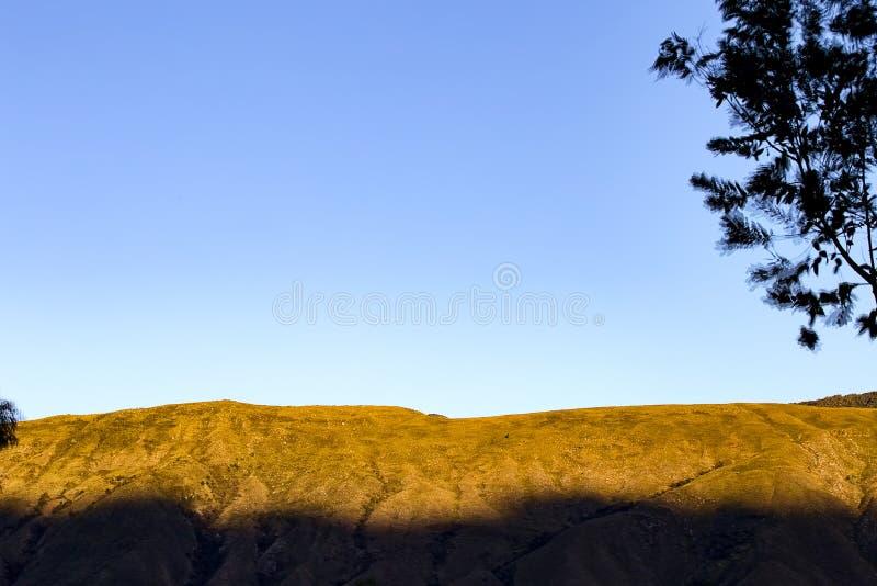 Montagne contre un ciel bleu clair au coucher du soleil photo libre de droits