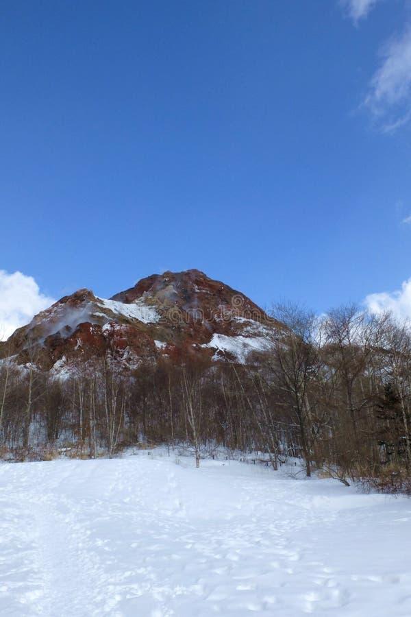 Montagne couverte par le fond de neige en ciel bleu dans un jour de soleil photographie stock libre de droits