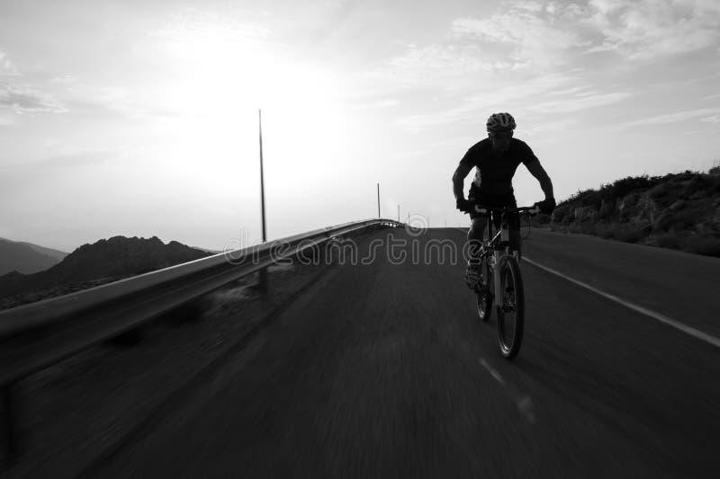 Montagne d'équitation d'homme de cycliste sur une route de montagne photographie stock