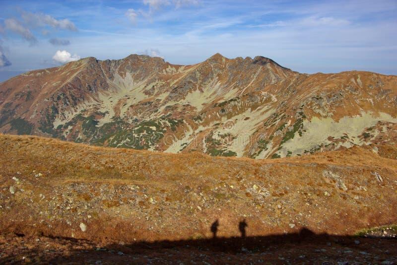 Montagne d'automne colorée à l'orange et aux silhouettes des personnes photographie stock libre de droits