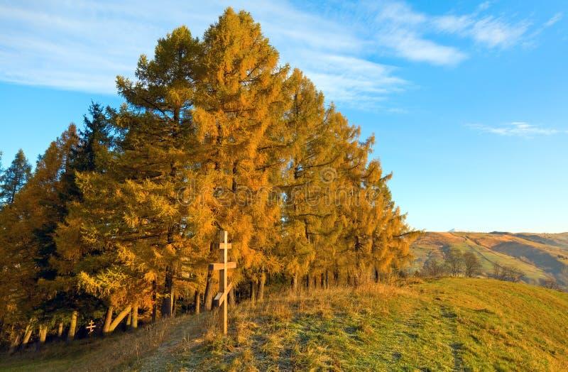 Montagne de matin d'automne et croix en bois image stock