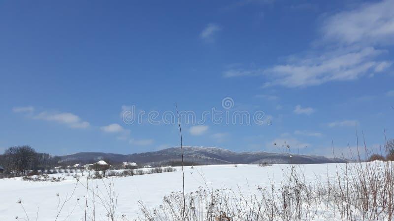 Montagne de neige sur le ciel ensoleillé bleu photographie stock libre de droits
