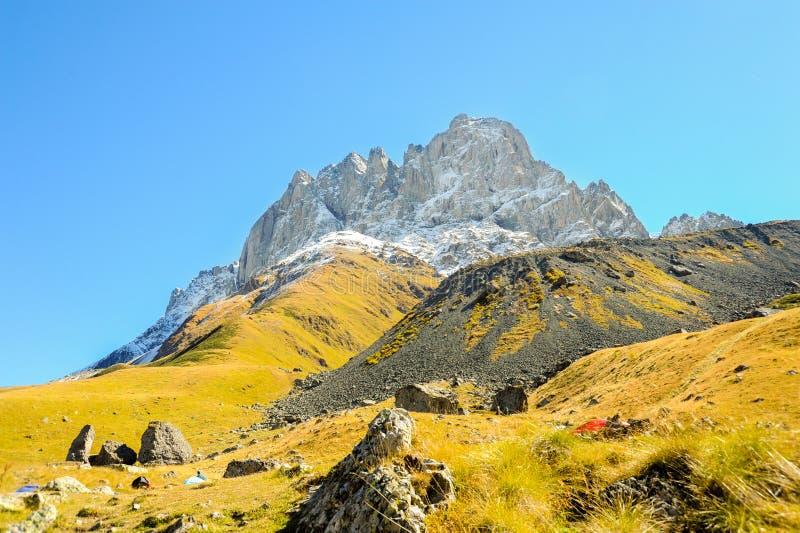 Montagne di Caucaso di estate, di erba verde, di cielo blu e di neve su Chiukhebi di punta immagini stock libere da diritti
