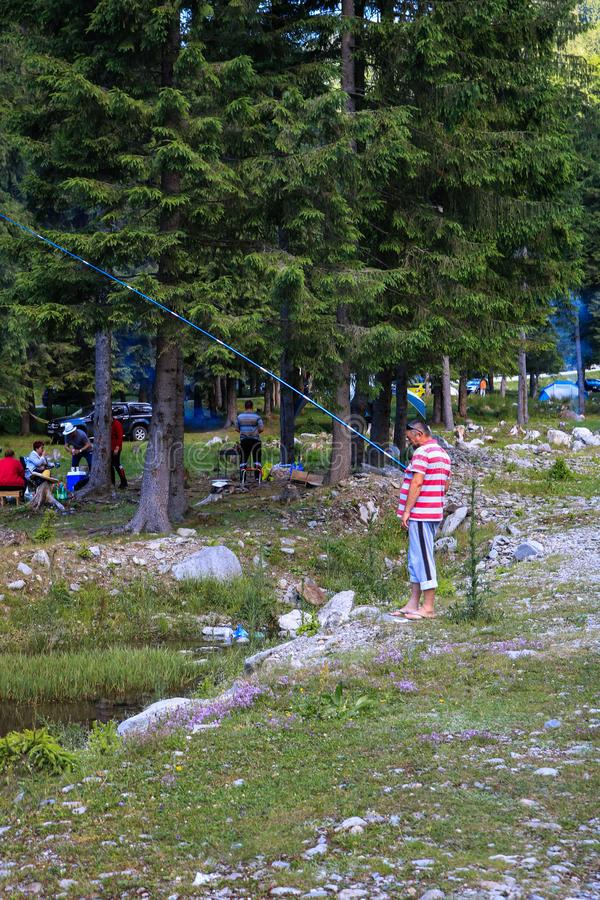 Montagne di Iezer - Romania - 2019 Pesca dell'uomo in The Creek della diga di Rausor nelle montagne di Iezer fotografie stock libere da diritti