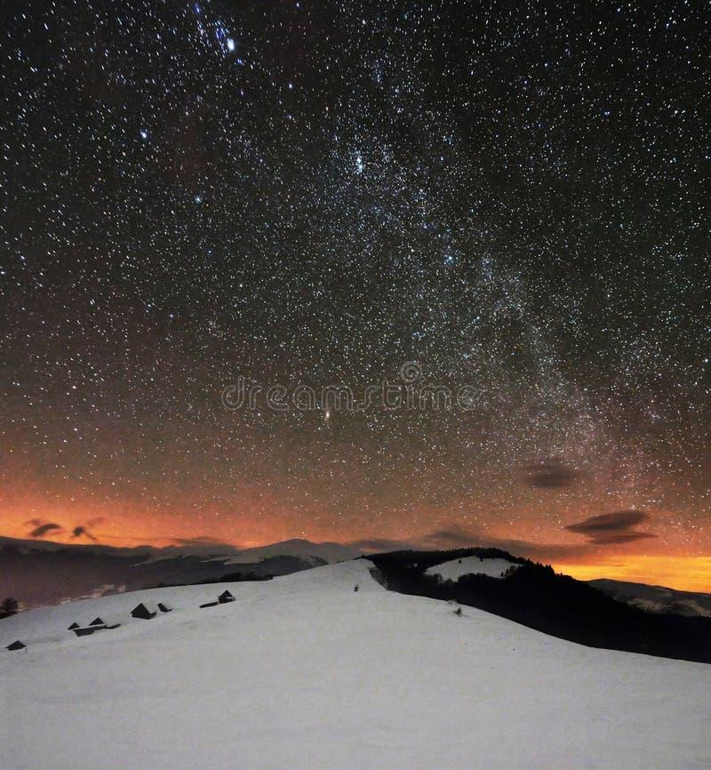 Montagne di inverno sotto il cielo nuvoloso stellato immagini stock
