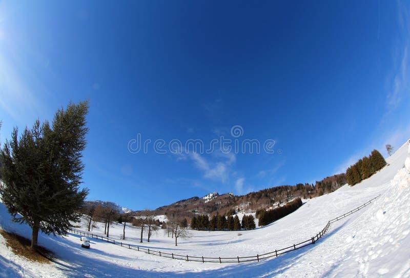 montagne di panorama con l'ampia lente di occhio del pesce e la neve bianca fotografia stock libera da diritti