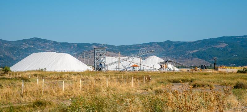 Montagne di sale che è raccolto con il macchinario pesante e il conve fotografie stock