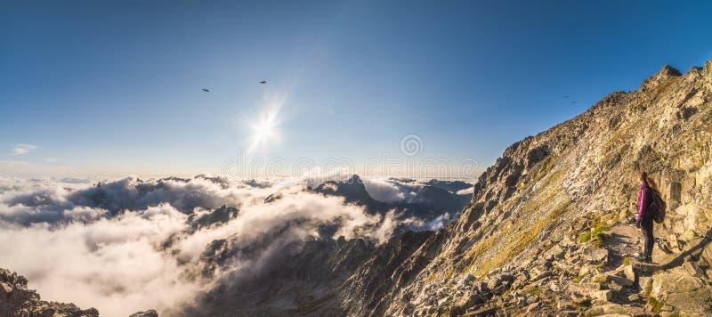 Montagne di sguardo turistiche con l'inversione al tramonto fotografia stock