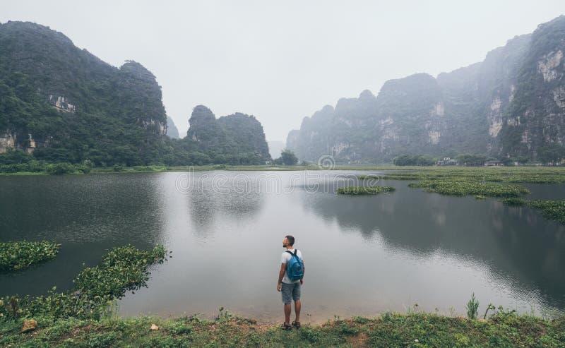 Montagne di trascuratezza del calcare dell'uomo caucasico nella provincia di Ninh Binh, Vietnam giorno nuvoloso fotografia stock libera da diritti