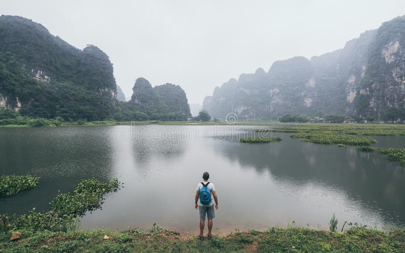 Montagne di trascuratezza del calcare dell'uomo caucasico nella provincia di Ninh Binh, Vietnam giorno nuvoloso immagine stock
