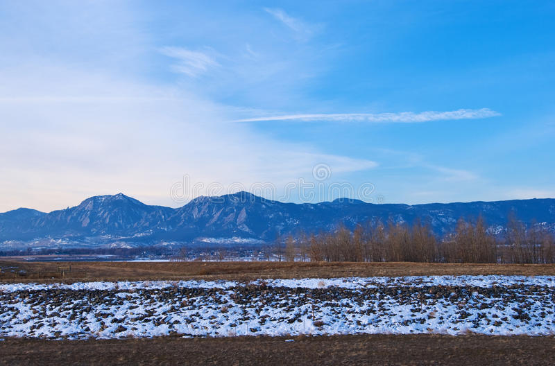Montagne distanti, Snowbank ed alberi fotografie stock