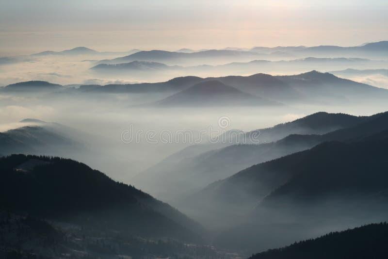 Montagne e montagne, cresta e nuvole basse fotografie stock libere da diritti