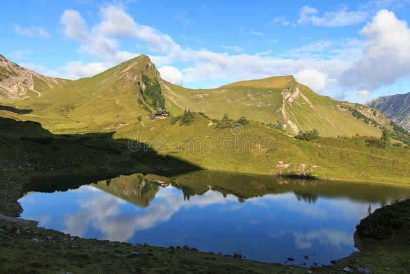 Montagne et hutte alpine avec la réflexion dans le lac photo stock