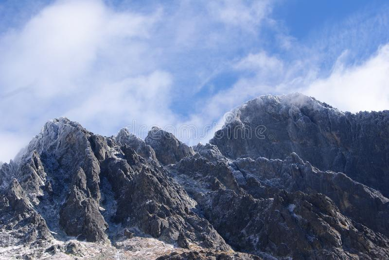 Montagne ghiacciate in cielo nuvoloso fotografia stock