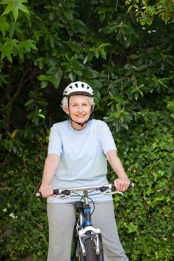 Montagne mûre de femme faisant du vélo à l'extérieur photos libres de droits