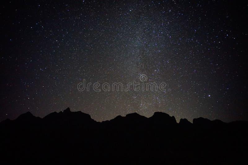 Montagne noire avec de pleines étoiles photos stock
