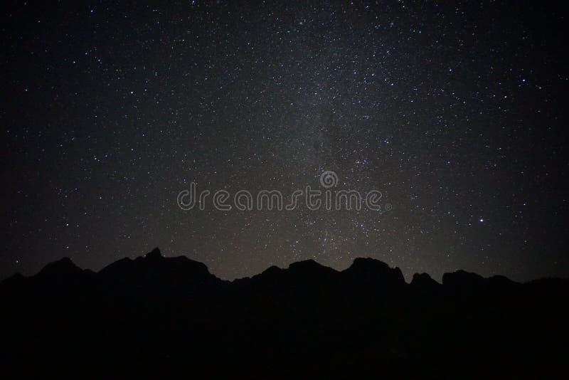 Montagne noire avec le ciel noir et les pleines étoiles images stock