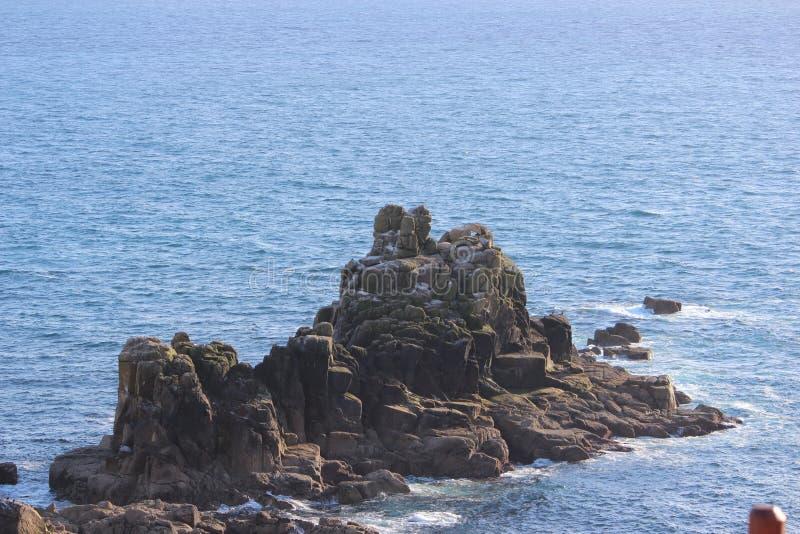 Montagne rocheuse dans l'océan photos stock