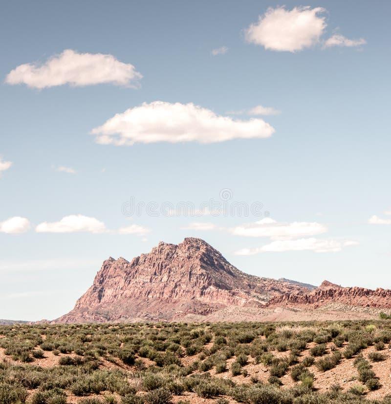 Montagne rouge lumineuse de roche avec de petits nuages en Arizona images stock