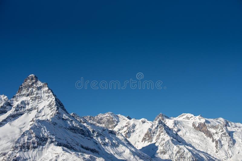 Montagnes d'hiver avec la neige et le ciel bleu dans le beau jour du soleil Station de sports d'hiver et concept de sport Montagn image libre de droits