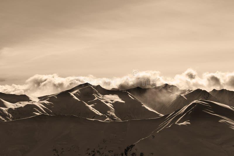 Montagnes d'hiver de soirée de sépia et nuages de lumière du soleil photo libre de droits