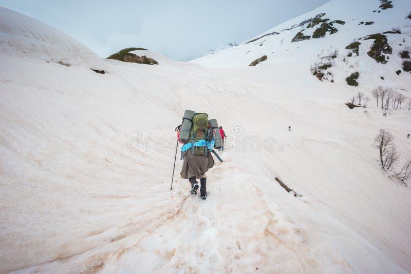 Montagnes d'hiver de voyageurs avec un sac à dos et des bâtons lifestyle photos stock