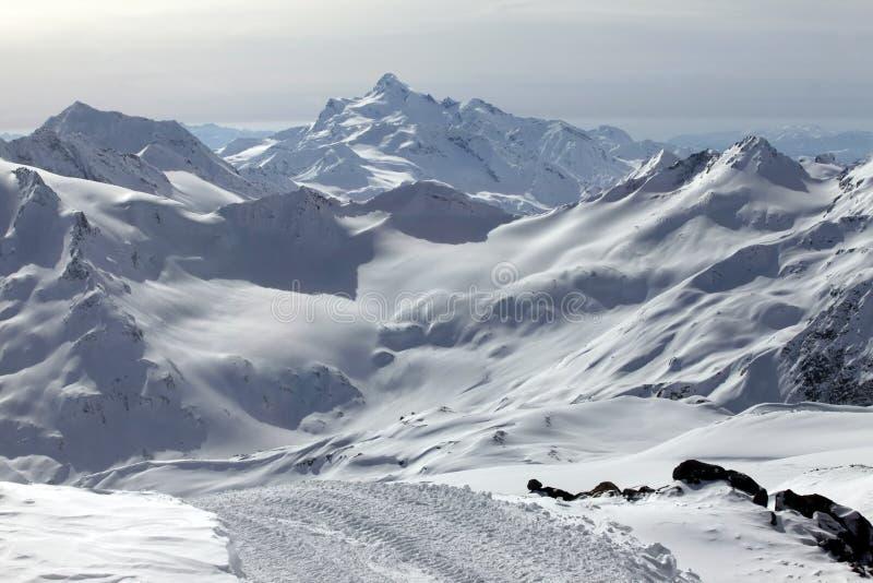 Montagnes dans la neige par temps nuageux photos stock