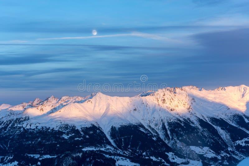 Montagnes de Milou pendant le coucher du soleil dans les alpes avec l'abo de pleine lune image libre de droits
