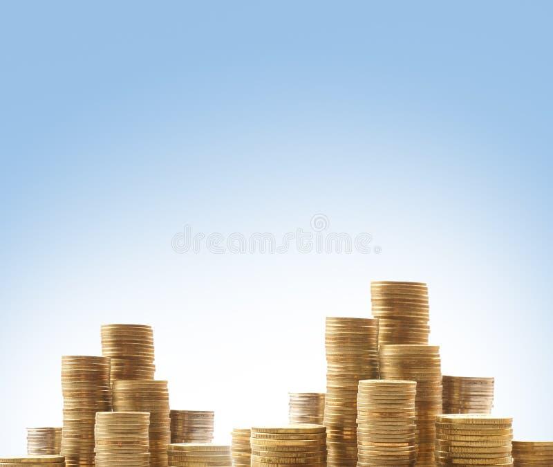 Montagnes des pièces de monnaie sur un fond bleu-clair photos libres de droits