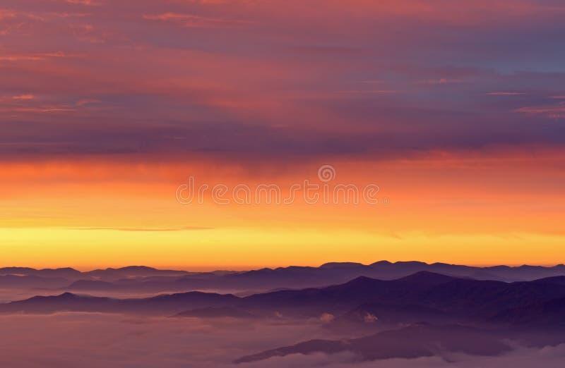 Montagnes fumeuses grandes de lever de soleil photos libres de droits