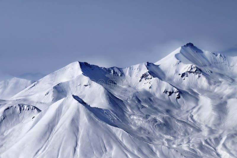 Montagnes neigeuses ensoleillées en brume et ciel nuageux à la soirée d'hiver photographie stock