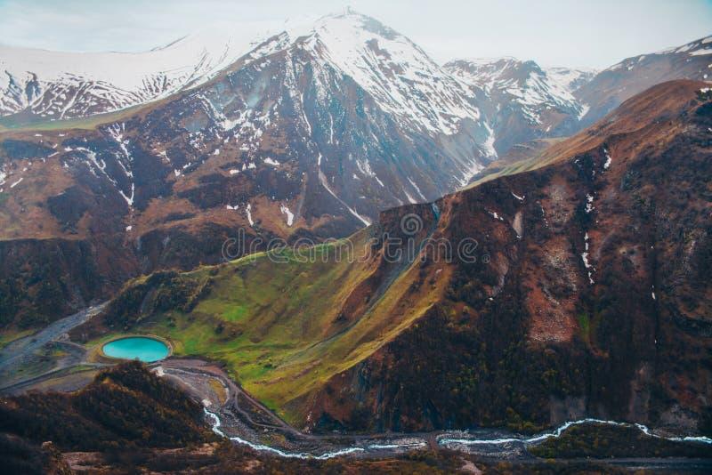 Montagnes neigeuses et lac bleu dans la vallée verte photographie stock libre de droits