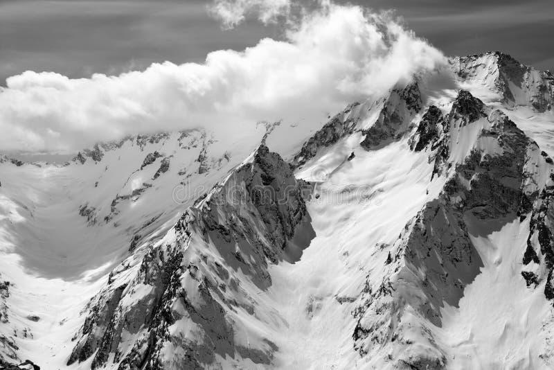 Montagnes noires et blanches d'hiver en nuages image stock