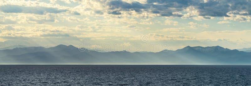 Montagnes par la mer en soleil image libre de droits