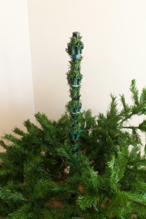 Montaje del árbol de navidad artificial foto de archivo