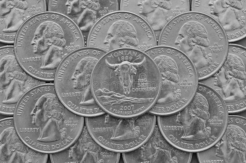 Montana State and coins of USA. Pile of the US quarter coins with George Washington and on the top a quarter of Montana State royalty free stock photos