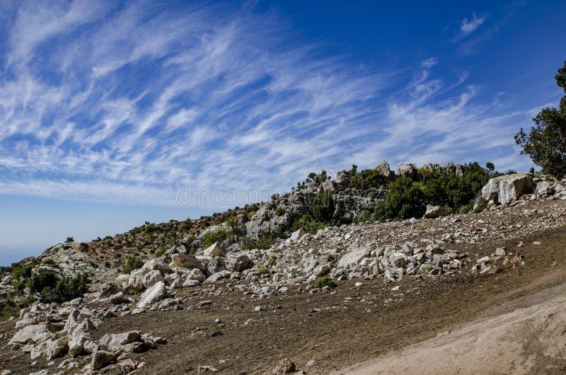 A montanha é espalhada com pedras e nas nuvens incredibly bonitas do fundo fotografia de stock