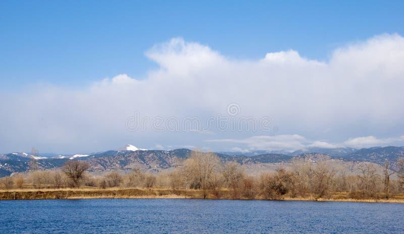 Montanha branca além de um lago azul brilhante fotografia de stock
