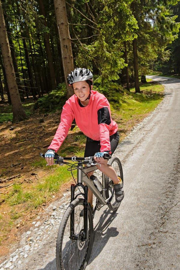 Montanha da mulher que biking no sorriso ensolarado da floresta fotografia de stock royalty free