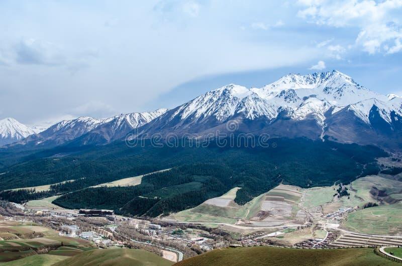 Montanha da neve e opini?o pequena da paisagem da vila fotografia de stock royalty free
