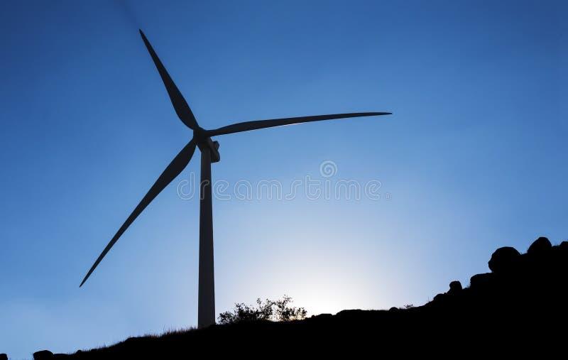 Montanha da silhueta do céu azul do moinho de vento da silhueta imagem de stock