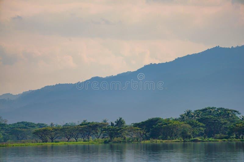 Montanha e lago com a nuvem original no lago Phayao, província do norte de Tailândia fotos de stock