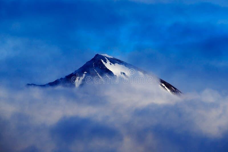 Montanha escura do inverno com neve nas nuvens, paisagem azul, Svalbard, Noruega imagens de stock