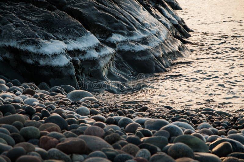 Montanha gelada pela água com as rochas no nascer do sol foto de stock